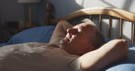 back side : Side view of a senior Caucasian man relaxing at home, lying on his back on his bed, with hands behind his head, napping in the sunlight, slow motion