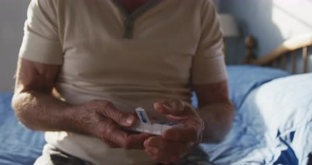 ev hayatı : Front view mid section of a senior Caucasian man at home in his bedroom, sitting on the bed taking tablets out of a weekly pill box after getting up in the morning, slow motion