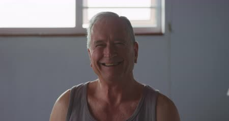rövid : Portrait of a senior Caucasian man relaxing at home in his bedroom, wearing a vest and looking to camera smiling, a sunlit window behind him, slow motion