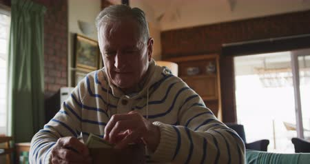 кошелек : Front view close up of a senior Caucasian man at home, sitting at the table in his dining room, looking at the money in his wallet and looking away thinking, slow motion Стоковые видеозаписи