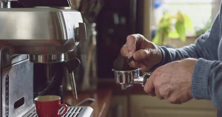 совок : Side view mid section of the hands of a senior Caucasian man relaxing at home, preparing coffee to use in an espresso machine, slow motion