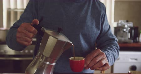 antecipação : Front view of a senior Caucasian man relaxing at home, pouring fresh coffee from a coffee percolator into his cup and smiling, slow motion