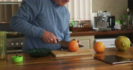 rubi : Side view of a senior Caucasian man relaxing at home, standing at the counter in his kitchen slicing a pink grapefruit in half on a chopping board with a sharp knife, slow motion Stock Footage