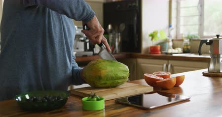 canteloupe : Side view mid section of a senior Caucasian man relaxing at home, standing at the counter in his kitchen carefully slicing a melon in half with a sharp knife, slow motion Stock Footage