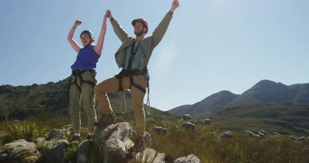 forro : Front view of young Caucasian couple holding hands in zip lining equipment, raising arms in the air on a sunny day in mountains, slow motion. Adventure Vacation in South Africa Stock Footage