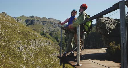 forro : Side view of young Caucasian couple talking, smiling and embracing while hiking in zip lining equipment on a sunny day in mountains, slow motion. Adventure Vacation in South Africa Stock Footage