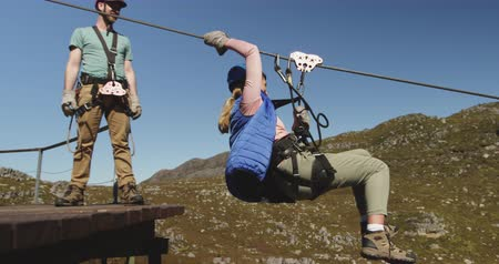 forro : Side view of a young Caucasian woman zip lining on a sunny day in mountains while a young Caucasian man is helping her and then watching her ride, slow motion. Adventure Vacation in South Africa