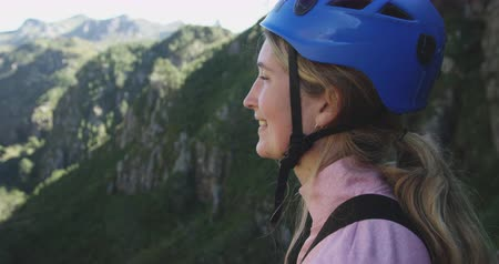 forro : Portrait of a young happy Caucasian woman in helmet admiring the view while out zip lining on sunny day in mountains, slow motion. Adventure Vacation in South Africa