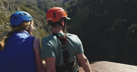 zip line : Rear view of young Caucasian couple in helmets admiring the mountain view, interacting and pointing in zip lining equipment on a sunny day, slow motion. Adventure Vacation in South Africa Stock Footage