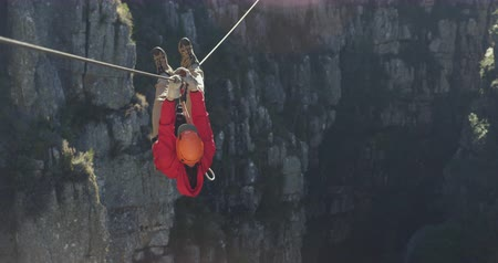 obložení : Rear view of a Caucasian man zip lining on a sunny day in mountains, climbing up the rope, slow motion. Adventure Vacation in South Africa
