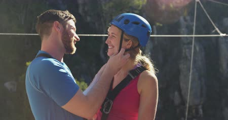 harness : Side view of young Caucasian couple in zip lining equipment, putting helmet on, kissing and smiling on a sunny day in mountains, slow motion. Adventure Vacation in South Africa Stock Footage