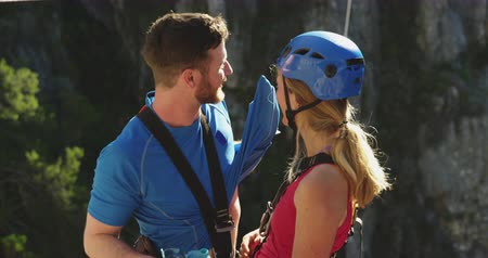 harness : Side view of young Caucasian couple in zip lining equipment talking and smiling on a sunny day in mountains, slow motion. Adventure Vacation in South Africa