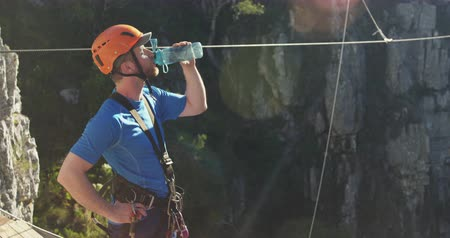 forro : Side view of a young Caucasian man in zip lining equipment taking a break and drinking water on a sunny day in mountains, slow motion. Adventure Vacation in South Africa Stock Footage