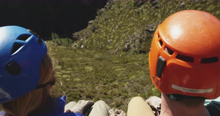 obložení : Over shoulder view of young Caucasian couple in helmets admiring the mountain view on a sunny day, slow motion. Adventure Vacation in South Africa