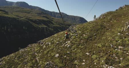 forro : High angle rear view of a young Caucasian man zip lining on a sunny day in mountains, slow motion. Adventure Vacation in South Africa