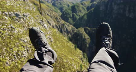 forro : Front view of legs of a man zip lining on a sunny day in the mountains, slow motion. Adventure Vacation in South Africa Stock Footage