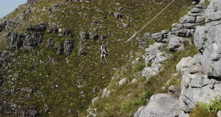 forro : Front view of a young Caucasian woman zip lining on a sunny day in mountains, slow motion. Adventure Vacation in South Africa