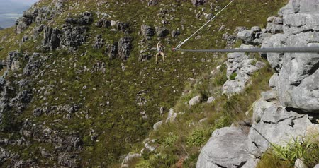 obložení : Front view of a young Caucasian man zip lining on a sunny day in mountains, slow motion. Adventure Vacation in South Africa