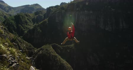 forro : Rear view of a young Caucasian man zip lining on a sunny day in mountains, slow motion. Adventure Vacation in South Africa