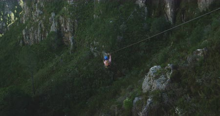 forro : Rear view of a young Caucasian woman zip lining on a sunny day in mountains, slow motion. Adventure Vacation in South Africa