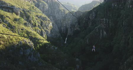 zipline : Front view of a young Caucasian man zip lining on a sunny day in mountains, slow motion. Adventure Vacation in South Africa