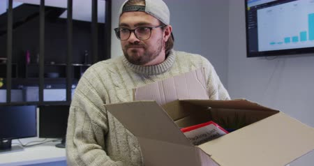 redundancy : Front view of a Caucasian man working in a creative office, wearing cap and glasses, carrying a cardboard box, slow motion