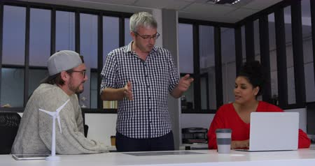 designing : Front view of a two Caucasian men and a mixed race woman working in a creative office, sitting at a desk with laptop computer, talking and brainstorming, slow motion