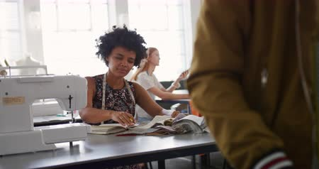 knutselen : Front view of a young African American Caucasian mixed race female fashion student working on a design in a studio at fashion college