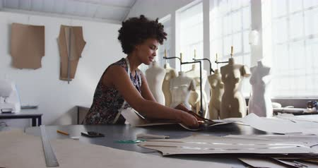 designing : Front view of a young African American Caucasian mixed race female fashion student working on a design in a studio at fashion college