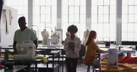 manequim : Front view of a young African American Caucasian mixed race female fashion student working on a design in a studio at fashion college