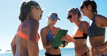 mulheres adultas meados : Female volleyball coach interacting with female players at beach 4k Vídeos