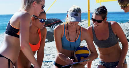 ajoelhado : Female volleyball coach interacting with female players at beach 4k Vídeos