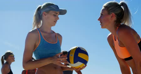 röplabda : Female volleyball coach interacting with female player at beach 4k