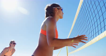 beach volleyball : Female volleyball players playing volleyball at beach 4k