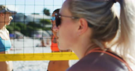 volleyball : Female vollleyball players interacting with each other at beach 4k