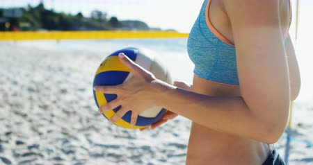 röplabda : Female volleyball player holding volleyball at beach 4k Stock mozgókép