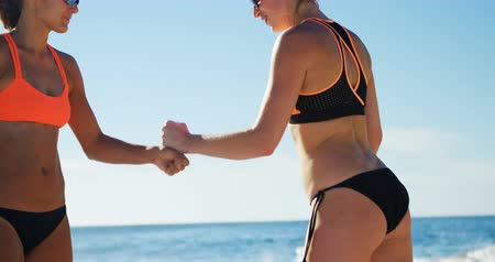 atleta : Female volleyball players giving fist bump to each other in the beach 4k Filmati Stock