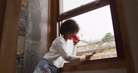 opvallen : Side view of a young mixed race woman with afro hair standing by a window at home, drinking a cup of coffee and using a smartphone, slow motion