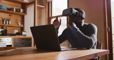 escritorio virtual : Front view close up of a young African American man wearing a VR headset and using a laptop sitting at the kitchen table at home, slow motion Archivo de Video