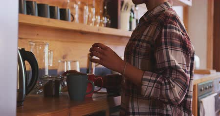 chaleira : Side view close up of a young mixed race woman with afro hair wearing a checked shirt making coffee on the hob in her kitchen
