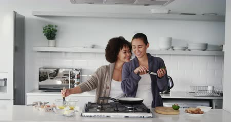 seks : Front view of a mixed race female couple enjoying time at home together, preparing breakfast in a kitchen, smiling, slow motion