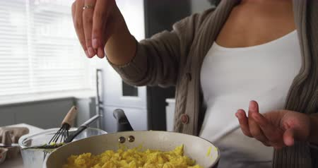 cooking salt : Front view of a mixed race woman enjoying time at home, preparing breakfast in kitchen, adding salt to scrambled eggs, slow motion