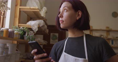 fazekas : Front view of a young Caucasian female potter with dark hair in a bob hairstyle standing by the window in a pottery studio, using a smartphone and looking out of the window, slow motion