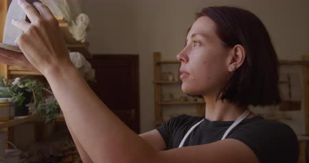 bob hairstyle : Side view close up of a young Caucasian female potter with auburn hair in a bob hairstyle standing by the window holding a pot and inspecting it in a pottery studio, slow motion Stock Footage