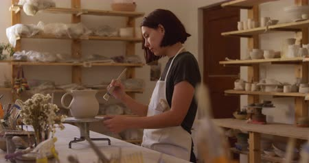 korsó : Side view of a young Caucasian female potter with dark hair in a bob hairstyle wearing an apron, standing at a work table turning a jug on a banding wheel and brushing it with glaze in a pottery studio, with pots on shelves in the background, slow motion Stock mozgókép