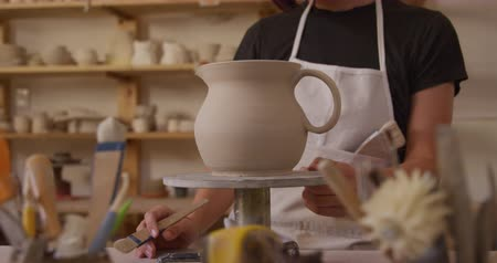 potter wheel : Front view close up of a young Caucasian female potter with dark hair in a bob hairstyle wearing an apron, standing at a work table turning a jug on a banding wheel and brushing it with glaze in a pottery studio, with pots and tools in the foreground, slo Stock Footage