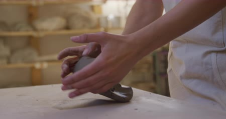 fazekas : Side view of a young Caucasian female potter with auburn hair in a bob hairstyle standing at a work table wearing an apron and kneading a lump of clay in a pottery studio, with shelves in the background, slow motion Stock mozgókép