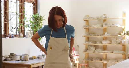 bob hairstyle : Portrait of a young Caucasian female potter with dark hair in a bob hairstyle putting on an apron, crossing her arms and looking to camera smiling in a pottery studio, with shelves in the background