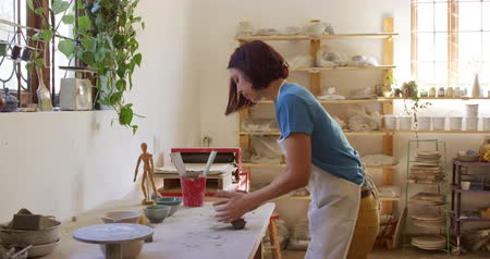 bob hairstyle : Side view of a young Caucasian female potter with dark hair in a bob hairstyle standing at a work table wearing an apron, kneading and cutting a lump of clay with a wire in a pottery studio, with shelves in the background Stock Footage