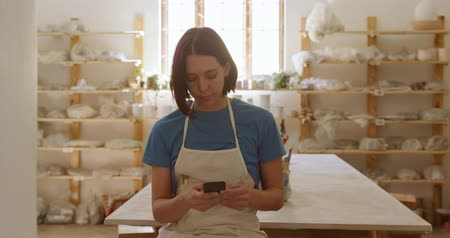 bob hairstyle : Front view of a young Caucasian female potter with dark hair in a bob hairstyle wearing an apron, standing using a smartphone and smiling in a pottery studio, with shelves and a window in the background